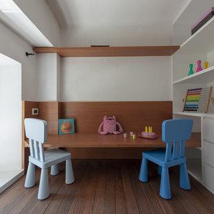 Esempio di una piccola cameretta per bambini da 4 a 10 anni minimalista con pareti bianche, parquet scuro e pavimento marrone