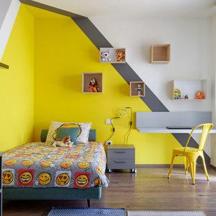 Ispirazione per una cameretta per bambini da 4 a 10 anni design di medie dimensioni con pareti multicolore, pavimento in legno massello medio e pavimento marrone