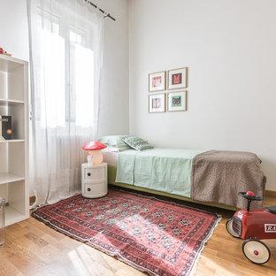 Esempio di una grande cameretta per bambini da 4 a 10 anni moderna con pareti bianche e pavimento in legno massello medio