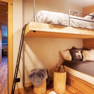 Foto di una cameretta per bambini stile rurale con pavimento in legno massello medio e pareti bianche
