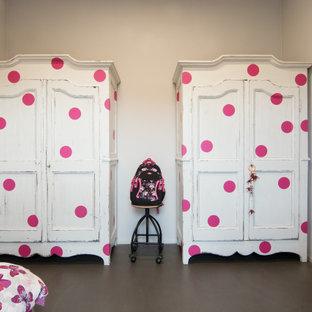 Esempio di una piccola cameretta per bambini da 4 a 10 anni industriale con pareti grigie, pavimento in cemento e pavimento grigio