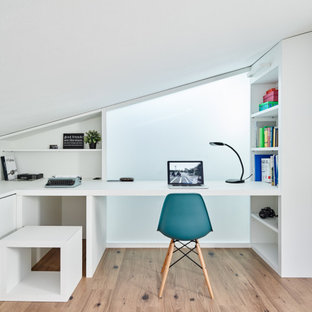 Immagine di una piccola cameretta per bambini design con pareti bianche, pavimento in laminato e pavimento beige