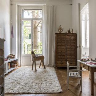 Ispirazione per una cameretta per bambini da 4 a 10 anni scandinava di medie dimensioni con pareti bianche, pavimento in legno massello medio e pavimento marrone