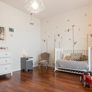Esempio di una cameretta per bambini da 1 a 3 anni scandinava di medie dimensioni con parquet scuro e pareti bianche