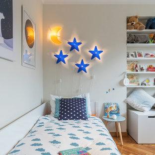 Esempio di una cameretta per bambini da 1 a 3 anni scandinava con pareti bianche e pavimento in legno massello medio