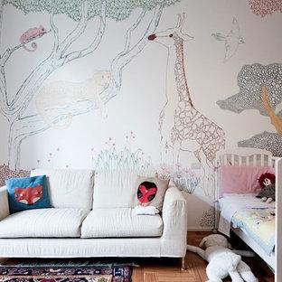Ispirazione per una cameretta per bambini da 1 a 3 anni scandinava di medie dimensioni con pavimento in legno massello medio, pareti multicolore e pavimento marrone
