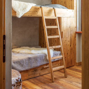Foto di una cameretta per bambini stile rurale con pareti grigie e pavimento in legno massello medio