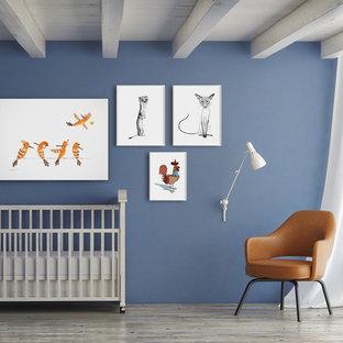 Imagen de habitación de bebé neutra nórdica, de tamaño medio, con paredes azules y suelo de madera pintada