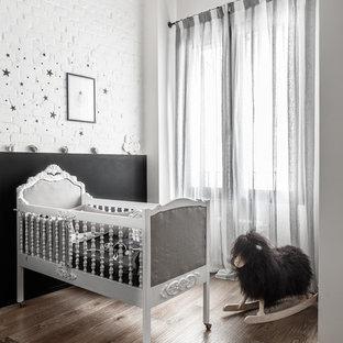 Esempio di una cameretta per neonati bohémian con pareti bianche, pavimento in legno massello medio e pavimento marrone