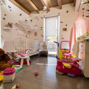 Foto de habitación de bebé niña actual, pequeña, con paredes blancas, suelo de baldosas de porcelana y suelo gris