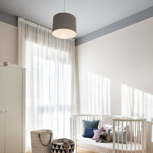 Inspiration for a medium sized contemporary gender neutral nursery in Milan with white walls and light hardwood flooring.