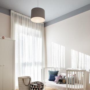 Immagine di una cameretta per neonati neutra contemporanea di medie dimensioni con pareti bianche e parquet chiaro