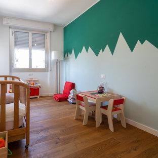 Idee per una cameretta per neonati design con pareti multicolore e pavimento in legno massello medio