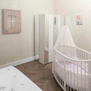Modelo de habitación de bebé niña actual, extra grande, con paredes beige y suelo de madera en tonos medios