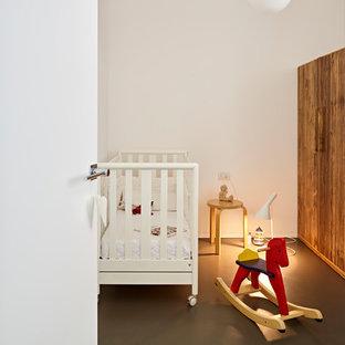 Cette photo montre une chambre de bébé neutre tendance de taille moyenne avec un mur blanc, béton au sol et un sol noir.