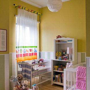 Esempio di una cameretta per neonati neutra nordica con pareti gialle e pavimento in laminato