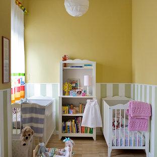 Idee per una cameretta per neonati neutra chic di medie dimensioni con pareti gialle, pavimento in legno massello medio e pavimento beige