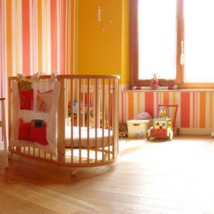 Réalisation d'une grand chambre de bébé fille minimaliste avec un mur multicolore et un sol en bois brun.