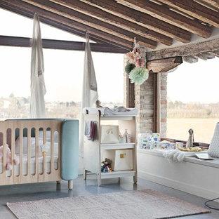 Imagen de habitación de bebé niña escandinava, de tamaño medio, con paredes blancas, suelo de cemento y suelo gris
