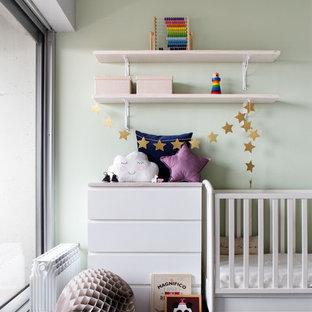 Diseño de habitación de bebé neutra contemporánea, de tamaño medio, con paredes verdes, suelo de cemento y suelo gris