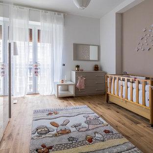 Immagine di una cameretta per neonati neutra classica di medie dimensioni con pareti multicolore, pavimento in legno massello medio e pavimento marrone