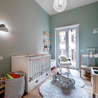 Esempio di una cameretta per neonati neutra contemporanea con pareti blu e parquet chiaro
