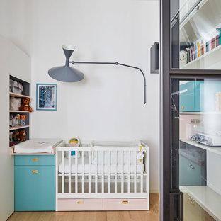 Ispirazione per una cameretta per neonati neutra minimal di medie dimensioni con pareti bianche, parquet chiaro e pavimento beige