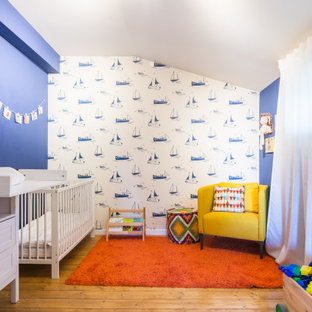 Inspiration for a large contemporary nursery in Other with blue walls, medium hardwood floors and brown floor.