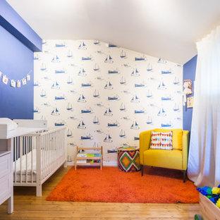 Immagine di una grande cameretta per neonati contemporanea con pareti blu, pavimento in legno massello medio e pavimento marrone