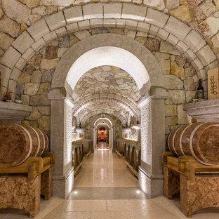 Réalisation d'une cave à vin chalet de taille moyenne avec un sol en calcaire et un sol rose.