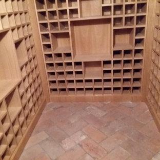 Inspiration pour une cave à vin traditionnelle de taille moyenne avec un sol en carreau de terre cuite, un présentoir et un sol rose.