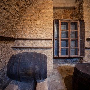 Diseño de bodega de estilo de casa de campo, de tamaño medio, con suelo de piedra caliza, vitrinas expositoras y suelo beige