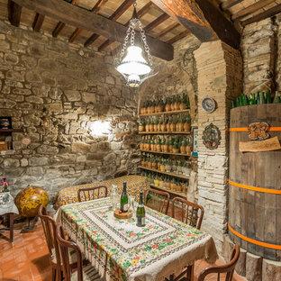 Inspiration för en liten lantlig vinkällare, med klinkergolv i terrakotta, vindisplay och orange golv