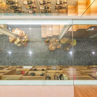 Immagine di una cantina di medie dimensioni con portabottiglie a vista e pavimento nero