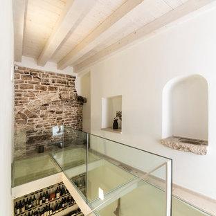 Immagine di una piccola cantina minimalista con pavimento in pietra calcarea, portabottiglie a vista e pavimento beige