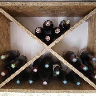 Imagen de bodega campestre, de tamaño medio, con suelo de baldosas de terracota, botelleros de rombos y suelo rojo
