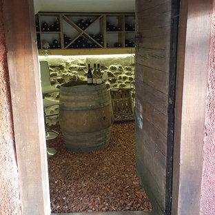 Foto de bodega de estilo de casa de campo, de tamaño medio, con suelo de baldosas de terracota, botelleros de rombos y suelo rojo
