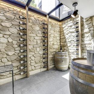 Exemple d'une grand cave à vin méditerranéenne avec béton au sol, un sol gris et un présentoir.