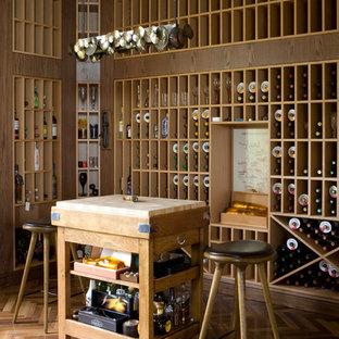 Ejemplo de bodega actual, grande, con suelo de madera en tonos medios y botelleros