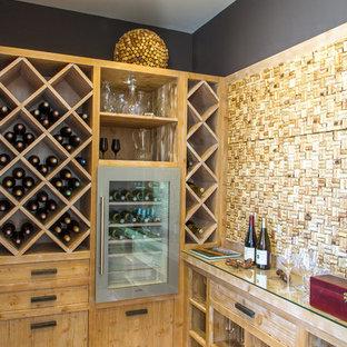 Foto de bodega actual, de tamaño medio, con botelleros de rombos y suelo de madera clara
