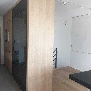 Immagine di una cantina minimal di medie dimensioni con parquet chiaro, portabottiglie a vista e pavimento marrone