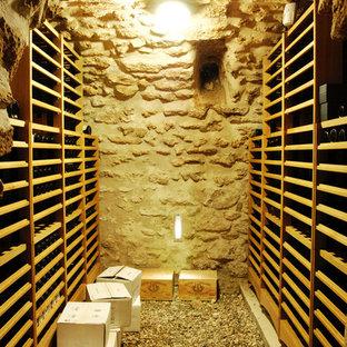 Exemple d'une cave à vin tendance avec des casiers et un sol gris.