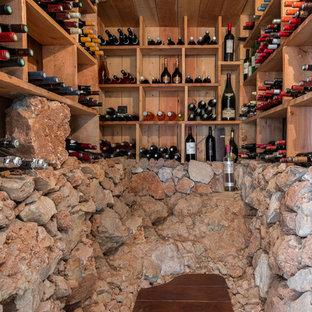 Inspiration pour une cave à vin méditerranéenne avec un sol en bois foncé, des casiers et un sol marron.
