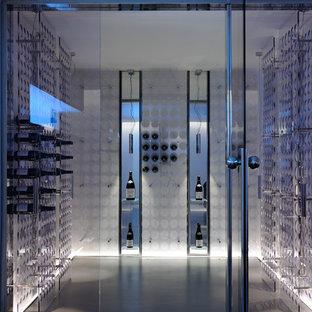 Foto på en funkis vinkällare, med betonggolv och vinhyllor