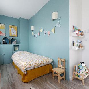 Aménagement d'une chambre d'enfant de 1 à 3 ans scandinave avec un mur bleu et un sol beige.