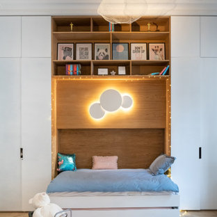Photo of a medium sized contemporary children's room for girls in London with white walls, light hardwood flooring and beige floors.