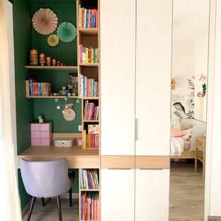 Esempio di una cameretta per bambini da 4 a 10 anni moderna di medie dimensioni con pareti verdi, pavimento in laminato, pavimento beige e carta da parati
