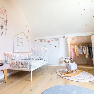 Cette image montre une chambre d'enfant de 1 à 3 ans nordique avec un mur blanc, un sol en bois clair et un sol beige.