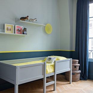 Idée de décoration pour une chambre d'enfant design avec un mur bleu, un sol en bois brun et un sol marron.
