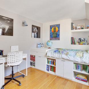 Exemple d'une chambre d'enfant tendance avec un mur blanc, un sol en bois brun et un sol marron.